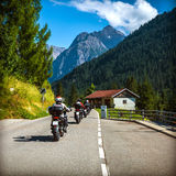 Group of bikers on the road in Alps. Extreme sport, moto tour along European mountains, beautiful landscape, travel and tourism concept Stock Images