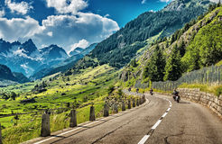 Group of bikers touring European Alps. Motorcyclists on mountainous road, enjoying ride, summertime activities, wonderful mountain landscape, extreme Royalty Free Stock Image