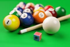 Group of billiard colored balls, cue and chalk on green table Stock Photo