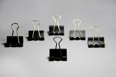 Group of binder clips. On white paper royalty free stock photography