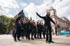 Group of Black Lives Matters protesters in front of Sir Winston Churchill Monument statue recording video clip holding their fists