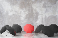 Group of black and one red umbrella Stock Photos