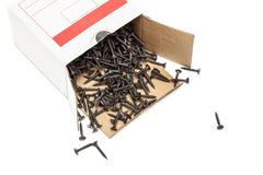 Group of black screws in a box. Group of black screws for fixing drywall on metal profiles, in a paper box Royalty Free Stock Image