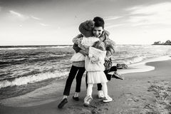 Three funny smiling laughing Caucasian children kids friends playing running on ocean sea beach royalty free stock photos