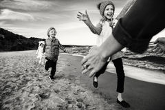 Three funny smiling laughing Caucasian children kids friends playing running on ocean sea beach stock photos