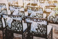 The back side of black wooden chairs with white organza sash decoration for beach wedding venue. A group of black wooden chairs decorated with white organza sash Royalty Free Stock Image