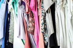 Woman blouse hanging in the closet. Group of blouses hung for a long time, with dust, in the closet stock photos