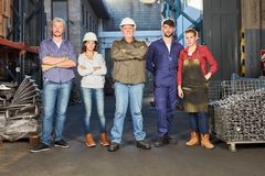 Group of blue collar workers as team. Group of blue collar workers as successful team in metal factory stock photo