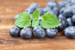 Group of blueberries with leaves on wood Stock Photos