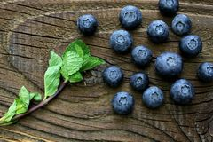 Blueberries with some mint leaves on antique wooden table. Group of blueberries and some mint leaves on antique table top view photo royalty free stock photos