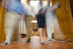 Group of blurred people walking through open doors Stock Image