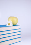 Group of books. Group of blue book, yellow apple and white flowers Royalty Free Stock Photo