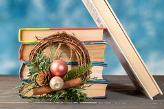 Group of books on a wooden surface with a Christmas wreath folded vertically stock image