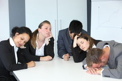 Group of bored demotivated businespeople. Group of diverse bored demotivated businespeople in a meeting seated at a table n the office napping with their eyes royalty free stock photos