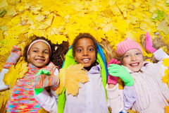 Group of boy and girls in the autumn leaves. Close shoot of a group of three diverse little children two girls and boy laying together on the ground covered with Stock Photo
