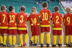 Group of boys football soccer futsal players standing together. Youth school indoor soccer tournament competition. Kids watching s stock images