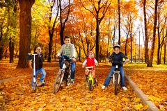 Group of boys and girls on bikes in park Stock Photo