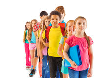 Group of boys and girls standing in the queue. Front view of the line of boys and girls standing in a queue African black and Caucasian Royalty Free Stock Photo