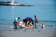 A group of children paddlers pulling a boat towards the shore a summer day. A group of boys paddlers pulling a boat towards the shore Royalty Free Stock Photography
