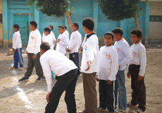 Group of Boys playing soccer in egypt. Group of boys playing soccer in street near school and having fun playing and doing activities together and helping each Royalty Free Stock Photography