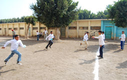 Group of Boys playing soccer in egypt. Group of boys playing soccer in street near school and having fun playing and doing activities together and helping each Royalty Free Stock Photos