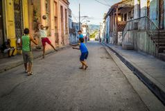 A group of boys playing soccer in santiag de cuba. A boy jumping up to catch a ball suspended in the air in a backstreet in santiago de cuba Royalty Free Stock Image