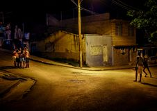 A group of boys playing in the street at night in santiago de cu. A group of boys counseling before starting the next move in a game in the night in santiago de Stock Images