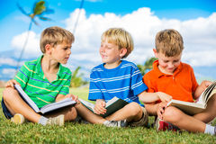 Group of Boys Reading. Happy Kids, Group of Young Boys Reading Books Outside Together after School Royalty Free Stock Photography