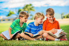 Group of Boys Reading. Happy Kids, Group of Young Boys Reading Books Outside Together after School Stock Photo