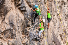Group Of Brave Climbers Climbing A Rock Wall Stock Image