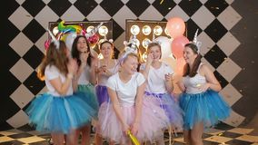 Group of bride friendgirls in a fairy unicorn costumes, colorful air skirts dancing throwing gold confetti on hipster. Girl s night out party stock video footage