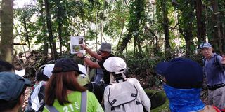 Group briefing in a forest. A leader shows a map from a magazine to a group of hikers in a  in singapore  forest aaia asia tengah bulim nature society team royalty free stock image