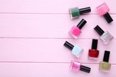 Group of bright nail polishes on pink stock image