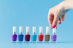 Group of bright nail polishes and woman hand Stock Image