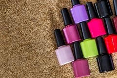 Bright nail polishes on wooden desk. Group of bright nail polishes on wooden desk Stock Images