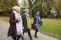 Group Of British Muslim Women Friends Walking Through Park Stock Photography