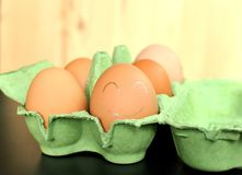 Group of brown chicken eggs in an green open formwork on natural wooden background. The closest egg is painted with white smiley f. Ace. Front view, close up stock photography