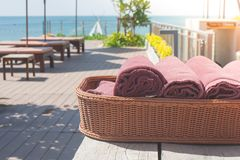 Group of brown towel setting on wooden basket beside swimming pool with seascape view in the background. stock photos