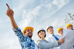 Group of builders and architects with blueprint. Business, building, teamwork and people concept - group of builders and architects in hardhats with blueprint on Stock Photo