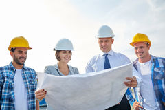 Group of builders and architects with blueprint. Business, building, teamwork and people concept - group of builders and architects in hardhats with blueprint on Royalty Free Stock Photo