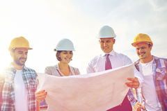 Group of builders and architects with blueprint. Business, building, teamwork and people concept - group of builders and architects in hardhats with blueprint on Stock Photos