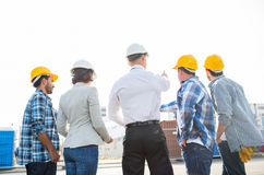 Group of builders and architects at building site. Business, building, teamwork and people concept - group of builders and architects in hardhats with blueprint Royalty Free Stock Photo