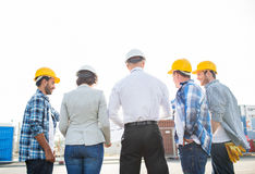 Group of builders and architects at building site. Business, building, teamwork and people concept - group of builders and architects in hardhats with blueprint Royalty Free Stock Images