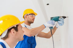 Group of builders with drill indoors Royalty Free Stock Images