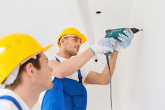 Group of builders with drill indoors Royalty Free Stock Photography