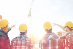 Group of builders in hardhats at construction site. Business, building, teamwork, development and people concept - group of builders in hardhats at construction royalty free stock photo