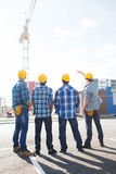 Group of builders in hardhats outdoors Stock Images