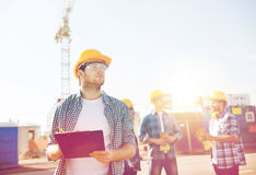 Group of builders in hardhats outdoors. Business, building, teamwork and people concept - group of builders in hardhats with clipboard outdoors Stock Photography