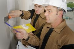 Group builders in hardhats with plastering tools indoors Stock Image