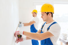 Group of builders with measuring tape indoors Stock Photos